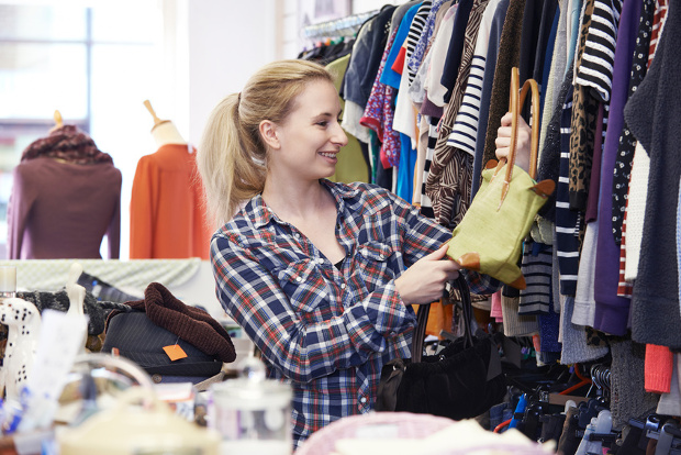 Female Shopper In Thrift Store Looking At Handbags